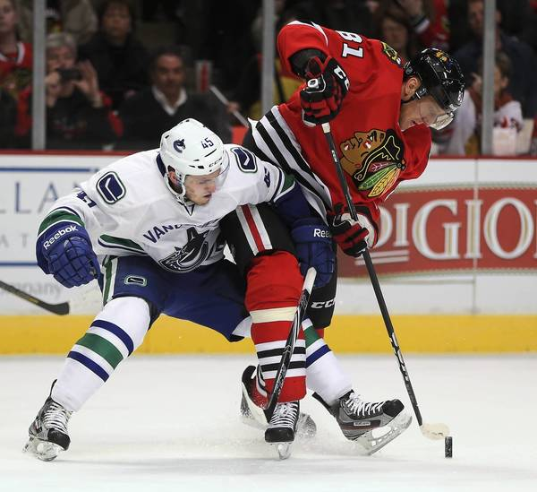 The Canucks' Jordan Schroeder and Marian Hossa battle for the puck in the first period.
