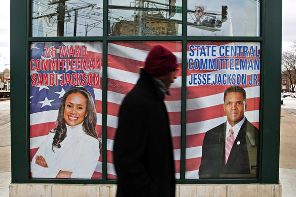 A man walks past a window decal showing Rep. Jesse Jackson Jr. and his wife Sandy at the former politicians' headquarters in Chicago on Saturday.