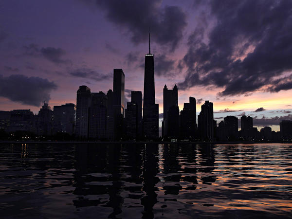 The sun sets behind the Chicago skyline as viewed from Lake Michigan.