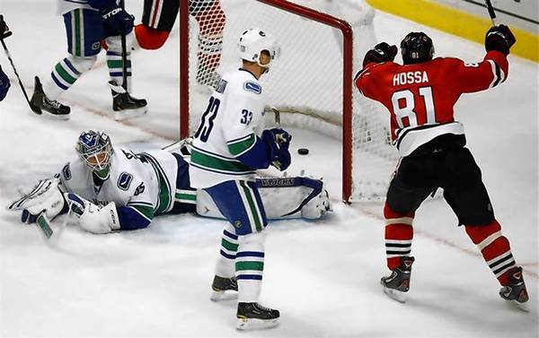 The Chicago Blackhawks' Marian Hossa (R) celebrates his goal on the Vancouver Canucks' Cory Schneider. The Blackhawks tied an NHL record set by the Anaheim Ducks in 2006 by going 16 consecutive games to start a season without a regulation loss. Chicago won in a shootout.