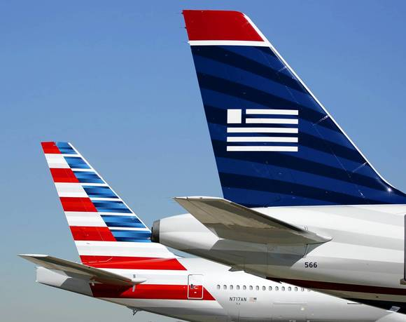 The tail sections of an American Airlines and US Airways aircraft are on the ramp  at Dallas-Ft Worth International Airport