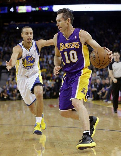 Steve Nash dribbles past the Golden State Warriors' Stephen Curry during a game in Oakland.