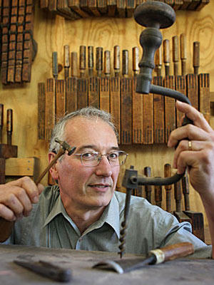 Woodworker Patrice Pinaquy poses for a portrait with some of his antique tools that he uses to build high-end furniture in his workshop in Los Angeles.
