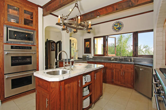 Beamed ceilings and arches continue in the kitchen of the house, which has three bedrooms and five bathrooms in 4,368 square feet.