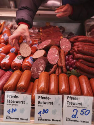 A shop assistant arranges horsemeat ham, wurst and sausage at the Schlemmer Hansel stand at the weekly open-air market in Hohenschoenhausen district on February 14 in Germany.