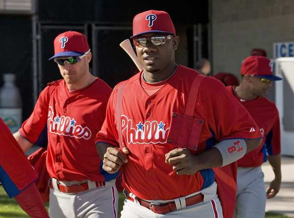Philadelphia Phillies' Pete Orr (L) and Ryan Howard (R) walk from the clubhouse to the practice field during a workout at the team's MLB spring training in Clearwater, Florida, February 19, 2013.