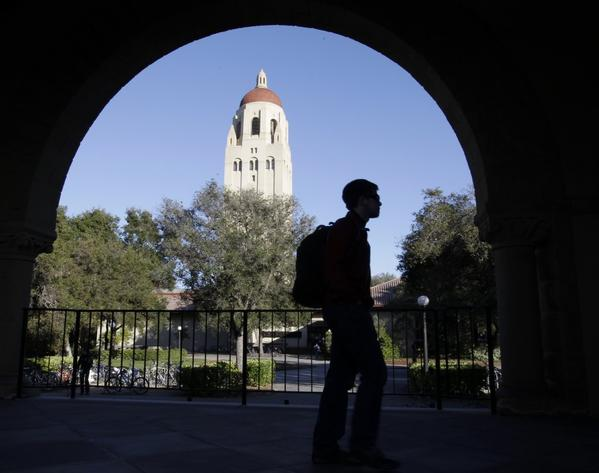 A student walks at Stanford University with Hoover Tower in the background.