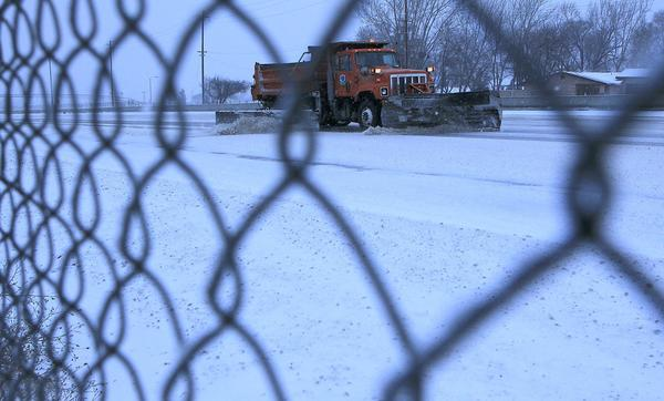 A Caltrans plow pushes snow on Interstate 5 in Lebec.