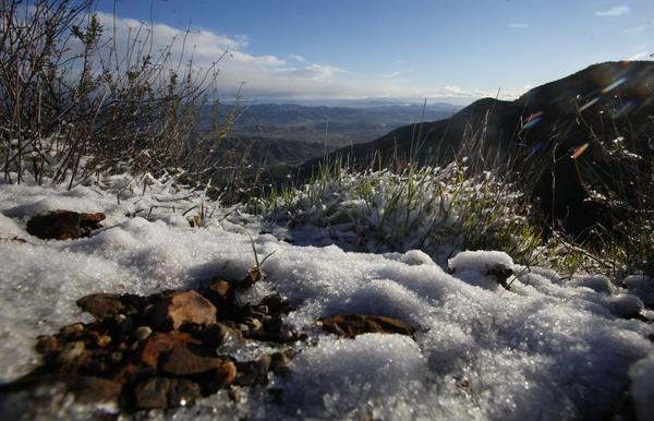 A layer of snow and ice covers the ground along North Main Divide Road on the ridge above Lake Elsinore after a fast-moving storm dropped snow and rain on Southern California.