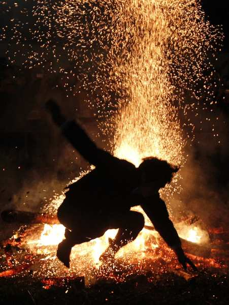 A Vietnamese man from the Pa Then minority group jumps into a fire during a ritual ceremony at the Vietnam Ethnic Minority Cultural Village, outside Hanoi February 20, 2013. The tribe with a population of 5,000, which resides in mountainous areas bordering China, organizes the annual fire-jumping ritual for adult men at the end of the harvest season. They believe that jumping into a fire without any protection will help them gain more special energy from God to challenge life's difficulties and fight evils.
