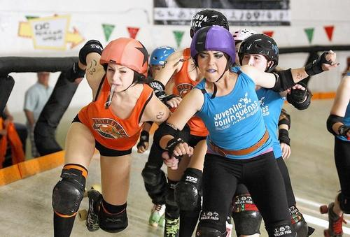 A member of the OC Roller Girls junior team, left, known as Onya Tushie,  tries to muscle her way around a Juvenile Dollinquent player during a matchup Saturday in Santa Ana.