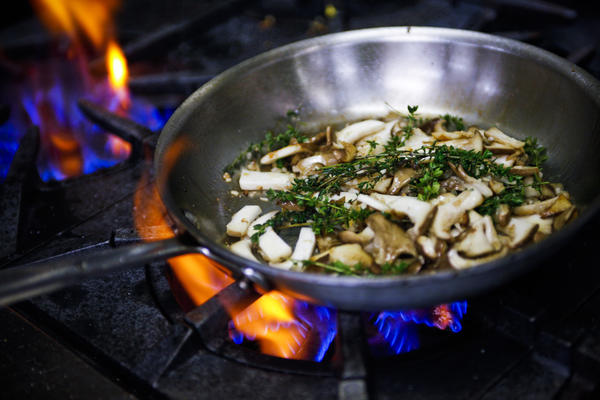 Wild mushrooms and spices simmer before being included in a mushroom and truffle risotto that is a featured dish Wolfgang Puck has put on the menu for the 2013 Academy Awards Governors Ball.