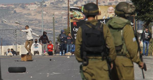 Palestinian demonstrators hurl stones at Israeli soldiers on Wednesday during clashes at the Huwwara checkpoint near Nablus in the West Bank.