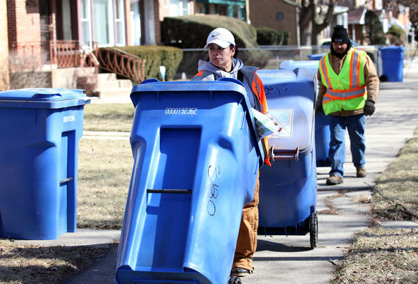 Department of Streets and Sanitation laborers Katherine Hernandez, left, and Minor Thomas deliver new recycling bins to households on West Jerome Street near the intersection of Jerome and Albany in Chicago. The recycling program will expand citywide to more than 131,000 new households.