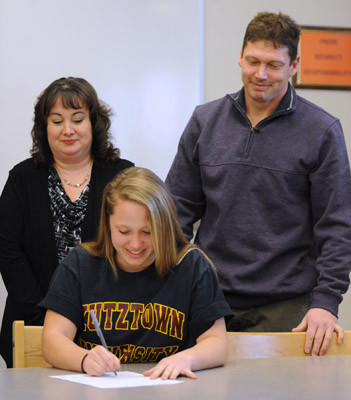 Megan Tiwold, a Northampton High School student, will play Field Hockey at Kutztown University next year. Her parents stand behind her at a signing ceremony held in the high school's library on Wednesday.
