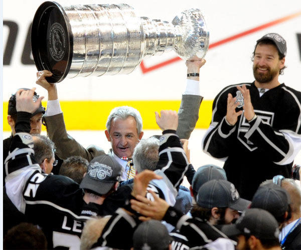 Kings Coach Darryl Sutter, shown hoisting the Stanley Cup trophy in June, says injuries have had a lot to do with the team's early struggles.