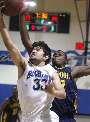 Burbank's Sarkis Karian beats the defense of Santa Monica's Chris Smith for a layup in the second quarter in a CIF Southern Section Division I-A second-round boys basketball playoff game at Burbank High School on Tuesday, February 19, 2013.
