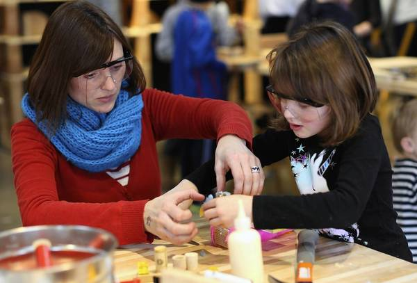 Magen Iwanski of St. Charles, helps her daughter Amelia Iwanski, 6, glue materials for an art piece while playing in the Tinkering Lab, a new permanent exhibit at the Chicago's Childrens Museum.