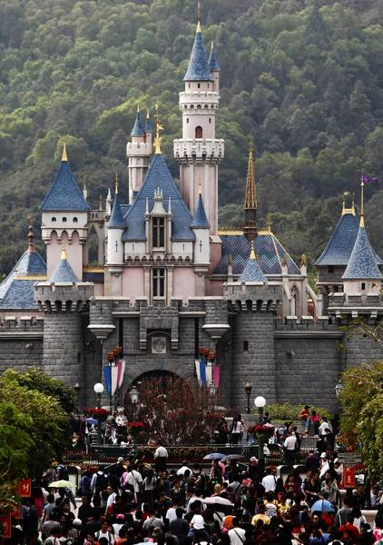 Visitors walk in front of a castle at Hong Kong Disneyland.