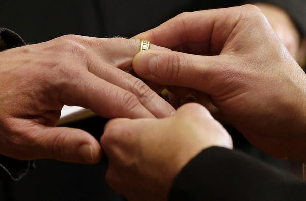 Thomas Rabe, right, places a wedding ring on Robert Coffman's finger during a marriage ceremony at City Hall in Baltimore, Md., where same-sex couples are now legally permitted to marry.
