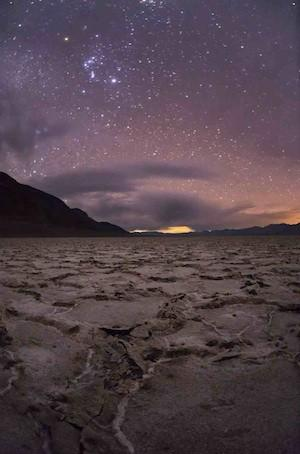 Stars and the Orion constellation in the night sky over Badwater at Death Valley National Park.