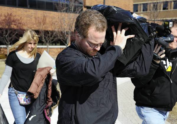 Terrance O'Brien uses a bag to shield himself from cameras Wednesday as he leaves DuPage County Jail after posting bond. He is one of three former Schaumburg police officers charged in a drug case.