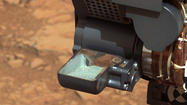NASA rover Curiosity scoops up first Martian rock sample