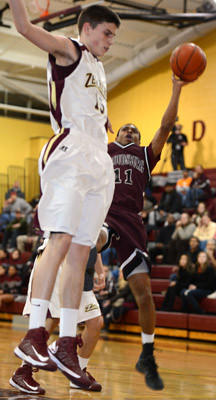 Stroudsburg's #11 David Clowney takes a shot and is defended by Whitehall's #15 Brett Radocha in their District 11 4A boys basketball playoff game held at Whitehall High School on Wednesday.