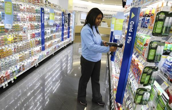 Price administrator Jenny Lawrence checks on cold and flu products Monday at a Walgreens drugstore in downtown Chicago.
