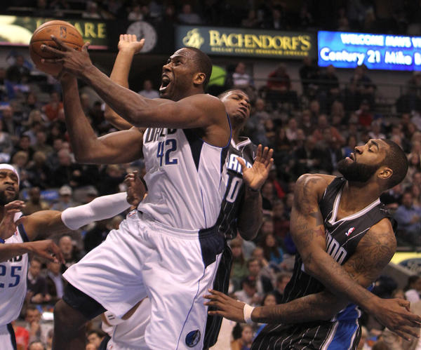 The Dallas Mavericks' Elton Brand (42) is hammered by the Orlando Magic's DeQuan Jones (20) and Kyle O'Quinn, right, during the first half at the American Airlines Center in Dallas, Texas