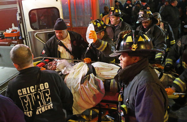 A victim is taken to an ambulance from the El station at Chicago Avenue and State Street in Chicago.