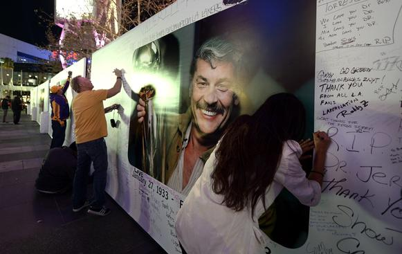 Fans sign a poster in honor of Lakers owner Jerry Buss, who died Monday at age 80, outside of Staples Center before a game against the Celtics on Wednesday night.