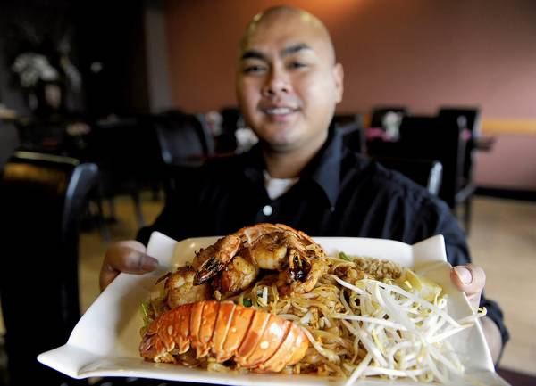 Veth Phoeng, a server at Thai Avenue Restaurant in South Whitehall Township, holds Lobster Pad Thai.