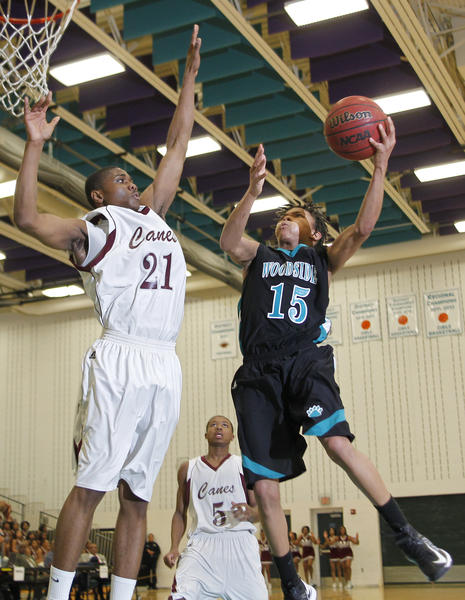Woodside's Jazz Johnson lays up a shot over Heritage's Troy Gibson during the first quarter of Monday's district tournament quarterfinal game.test