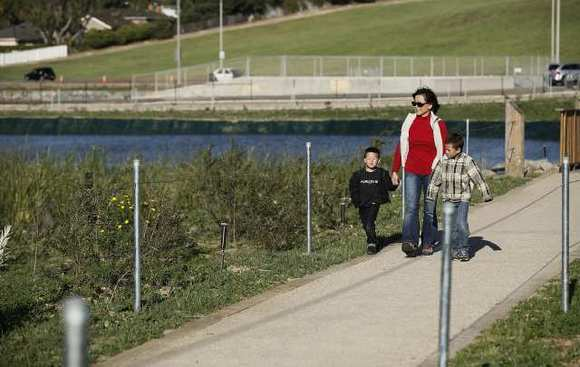 Lena Hayashi, with grandsons Drew, right, and Scott Hayashi walk along the paths during the ribbon-cutting ceremony Wednesday afternoon for the Fairview Park Wetlands & Riparian Habitat