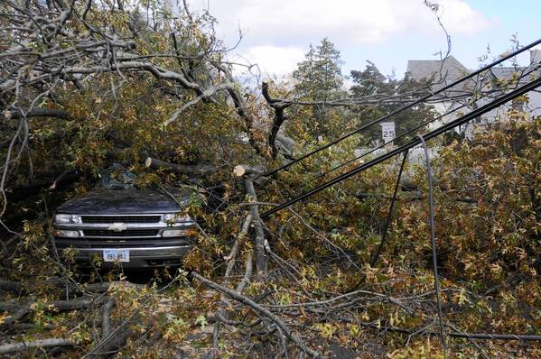 A car is crushed by a large tree on Judson Street in Fairfield, brought down by Storm Sandy.