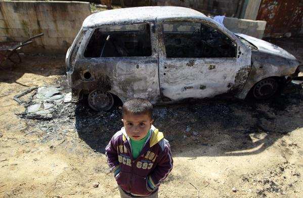 A Palestinian boy stands near a burnt car in the West Bank village of Kusra near Nablus February 21, 2013. Six Palestinian-owned cars were damaged in the West Bank village overnight, in what residents said was an attack by settlers from a near-by Jewish outpost. The Israeli army said it had received a complaint and is now investigating the incident.