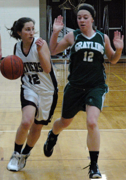Charlevoix senior guard Sydney Carlson (left) drives along the baseline as Grayling's Maddie Benardo defends during Wednesday's Lake Michigan Conference contest at the Charlevoix High School gym.