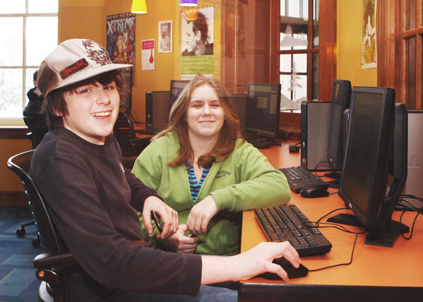 A glimpse through the library window brings a smile from Jared Lowell (left) and Emily Mercer, both 13 of Charlevoix, Wednesday, as they spend time at the Charlevoix Public Library, during a no school, snow day.