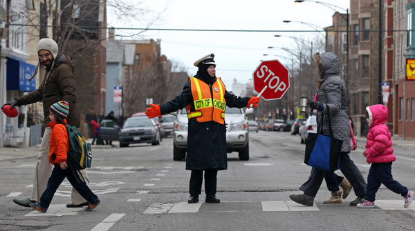 A crossing guard assists pedestrians at West Armitage Avenue at North Leavitt Street this morning