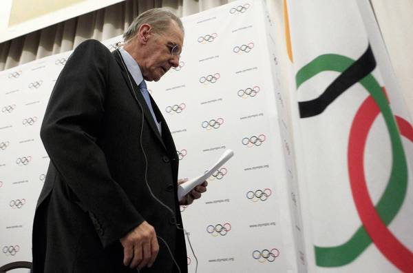 International Olympic Committee President Jacques Rogge leaves after a Feb. 13 news conference in Lausanne, Switzerland, where it was announced wrestling likely will be dropped from the 2020 Summer Olympics.
