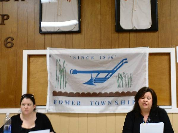Homer Township Clerk Linsey Sowa and Supervisor Pam Meyers discuss business during the Feb. 11 board meeting. Behind them are circa 1930s baseball jerseys donated to the township.