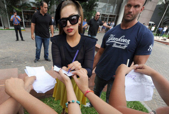 Lady Gaga (c) signs autographs to fans outside the hotel, in Asuncion, on November 26, 2012.