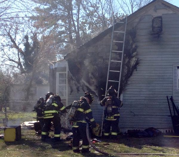 Firefighters work the scene of a midday house fire at 1312 36th St. in Newport News Thursday.