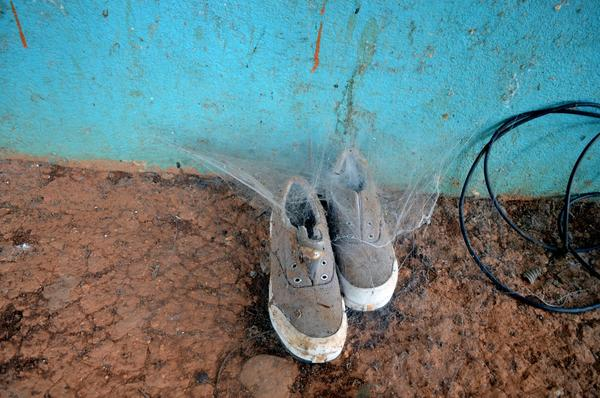 Cobwebs are taking over a pair of shoes left on a porch.