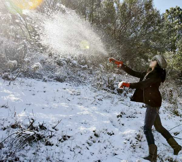 Katia Guerrero, 17 from Monrovia, plays in the snow at Angeles Crest Highway near Angeles Forest Highway in the Angeles National Forest above La Canada Flintridge on Wednesday, February 20, 2013.  Guerrero's older sister brought her up to the snow because today is her birthday. A fast-moving storm dumped snow at higher elevations overnight.
