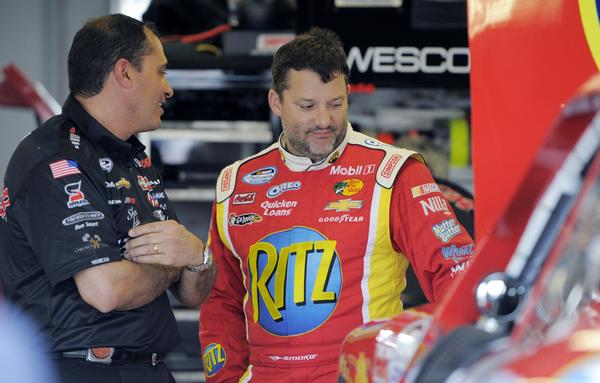 Tony Stewart (R) stands in his Nationwide Series garage at the Daytona International Speedway in Daytona Beach, Florida February 21, 2013. The Daytona 500 NASCAR Sprint Cup race is scheduled for February 24.