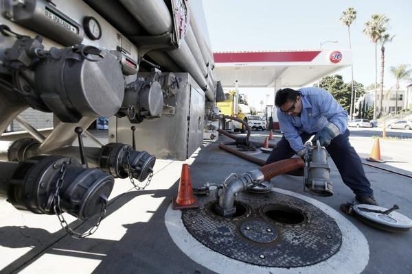 Freddy Lozoga fills an underground tank at a service station in Los Angeles. The one-month increase in Southern California gas prices is a record.