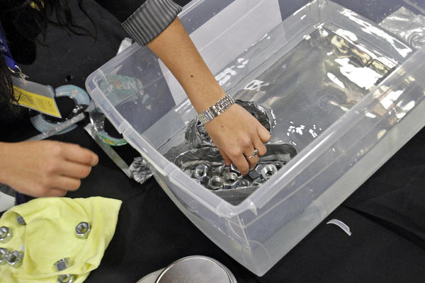 A student places weaights into a duct tape boat during Thursday's Engineering Career Day at Newport News Shipbuilding. Hundreds of area students participated in an engineering design contest and talked with professionals from NNS, Peninsula Engineers Council and NASA Langley Research Center.