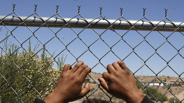 After being detained by the U.S. Border Patrol, a man rests his hands on a fence looking out to the United States from a Mexican customs station.